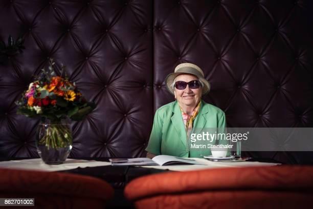 Ältere Lady mit Hut beim Kaffee trinken