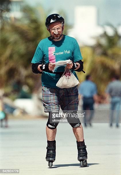 Älterer Mann / Senior beim InlineSkaten auf der Strandpromenade von Miami Er trägt Helm Nasenpflaster als Sonnenschutz Ellbogen Hand und Knieschützer...