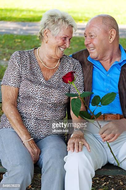 Älteres Senioren Ehepaar ist verliebt. Mann überreicht eine Rose.