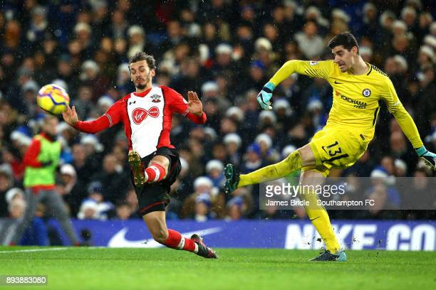 LtoR Manolo Gabbiadini of Southampton charges Thibaut Courtois of Chelsea FC during the Premier League match between Chelsea and Southampton FC at...