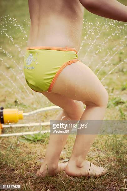 Lttle girl having fun with lawn sprinkler in the garten, partial view