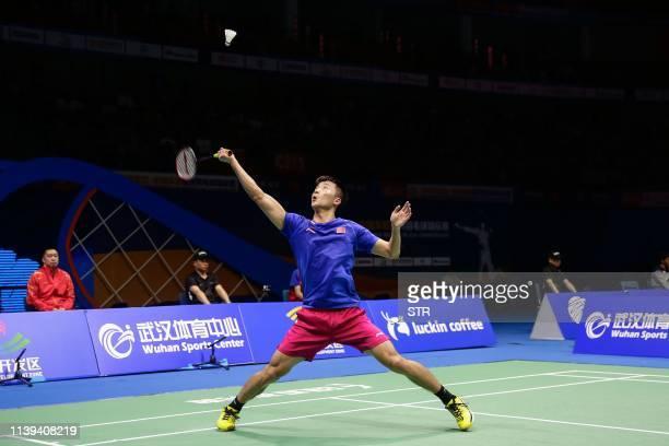 Lu Guangzu of China hits a return against Kento Momota of Japan during their men's singles quarterfinal match at the 2019 Badminton Asia...