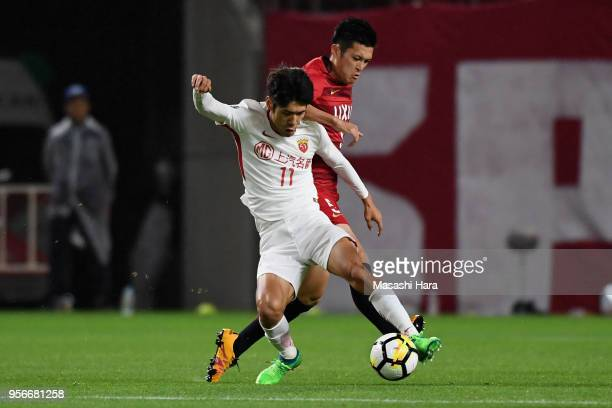 Lu Wenjun of Shanghai SIPG controls the ball under pressure of Naomichi Ueda of Kashima Antlers during the AFC Champions League Round of 16 first leg...