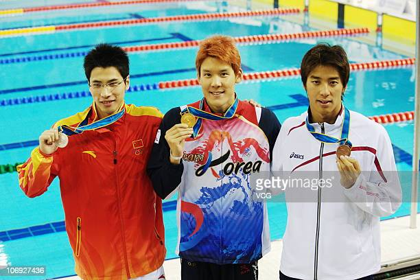 Lu Zhiwu of China Taehwan Park of South Korea and Takuro Fujii of Japan pose with the medals won in the Men's 100m Freestyle final at the Aoti...