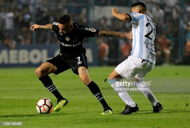 Luan Guilherme de Jesus Vieira of Brazilian Gremio disputes the ball with Rodrigo Aliendro of Argentinian Atletico Tucuman during their Copa...