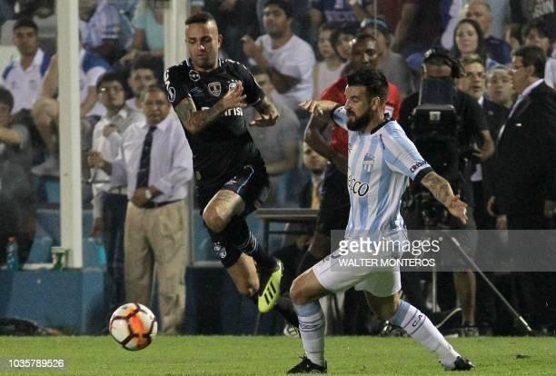 Luan Guilherme de Jesus Vieira of Brazil's Gremio vies for the ball with Jose San Roman of Atletico Tucuman during their Copa Libertadores football...