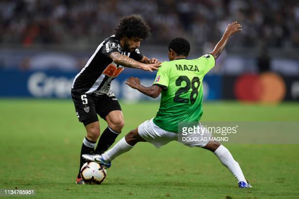 Luan of Brazil's Atletico Mineiro vies for the ball with Jader Maza of Venezuela's Zamora during their 2019 Copa Libertadores football match at...