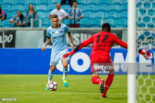 Luan of Gremio battles for the ball against Bryan Cortes of Deportes Iquique during the match Gremio v Deportes Iquique as part of Copa Bridgestone...