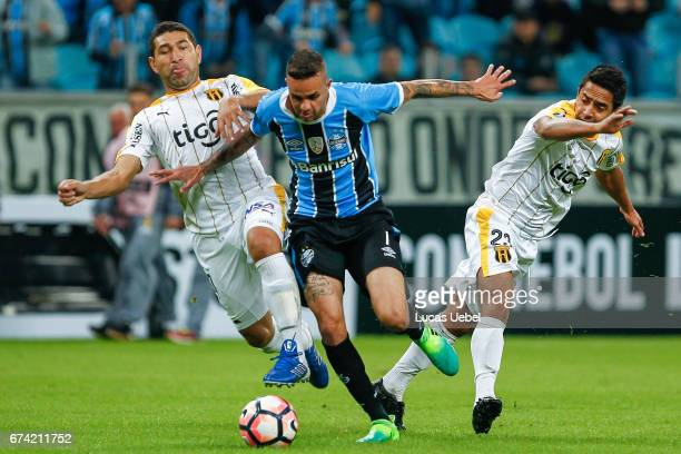 Luan of Gremio battles for the ball against Luis Cabral of Guarani during the match Gremio v Guarani as part of Copa Bridgestone Libertadores 2017 at...