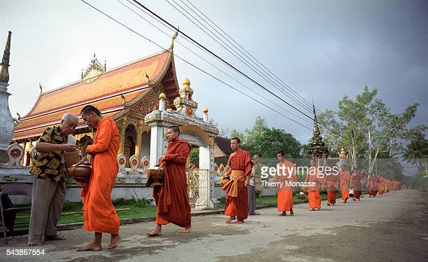 Luang Prabang, Lao People's Democratic Republic, August 2003. -- Monks and novices reiceve morning alms on the streets of the historic district....