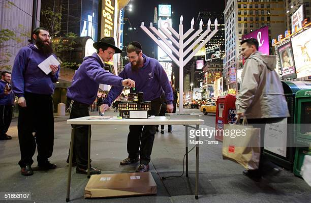 Lubavitch Hasidic Jewish rabbinical students spin dreidels in Times Square while celebrating the festival of Chanukah December 12 2004 in New York...