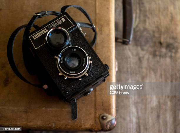 Lubitel 166 B old roll film camera seen on the background of vintage suitcase