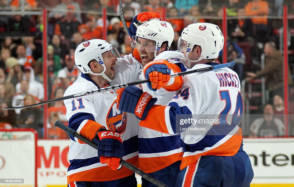 Lubomir Visnovsky #11, Colin McDonald #13, and Thomas Hickey #14 of the New York Islanders celebrate McDonald's second goal of the third period against the Philadelphia Flyers on March 28, 2013 at the Wells Fargo Center in Philadelphia, Pennsylvania. The Islanders won 4-3 in a shootout.