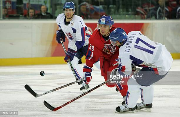 Lubomir Visnovsky of Slovakia fights for the puck with Jan Bulis of Czech Republic during the quarter final of the men's ice hockey match between...