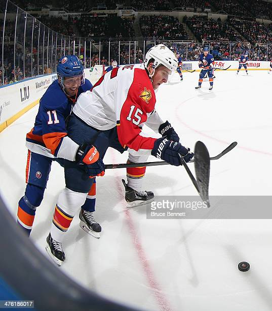 Lubomir Visnovsky of the New York Islanders hangs on to Drew Shore of the Florida Panthers at the Nassau Veterans Memorial Coliseum on March 2 2014...
