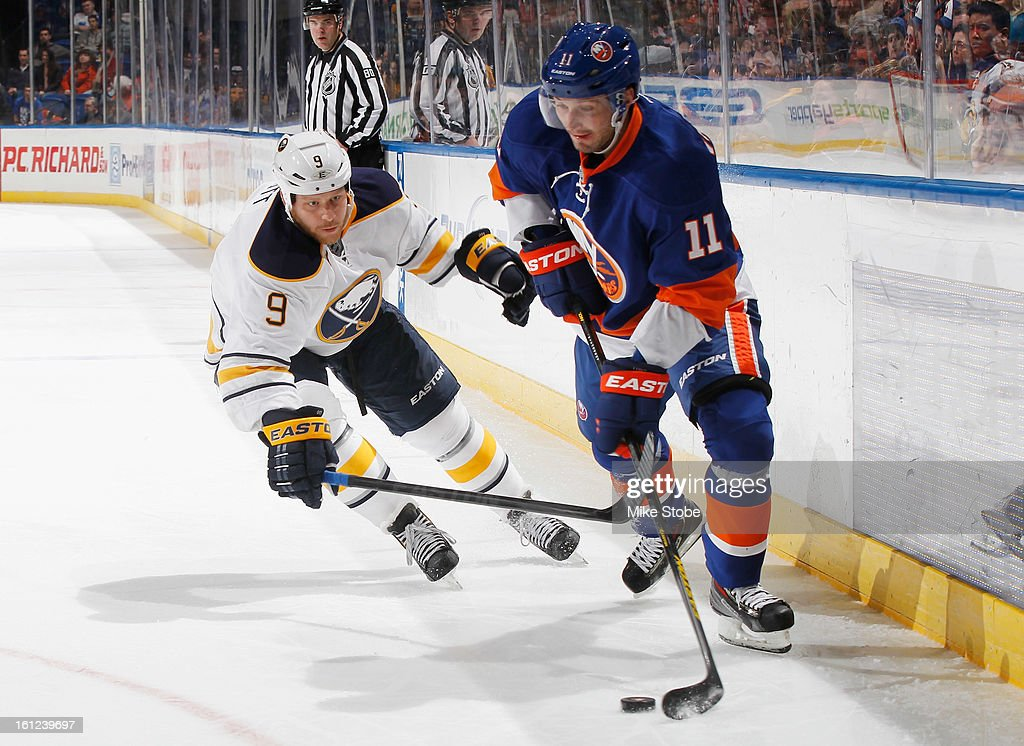 Lubomir Visnovsky #11 of the New York Islanders protects the puck against Steve Ott #9 of the Buffalo Sabres at Nassau Veterans Memorial Coliseum on February 9, 2013 in Uniondale, New York. The Sabres defeated the Islanders 3-2.
