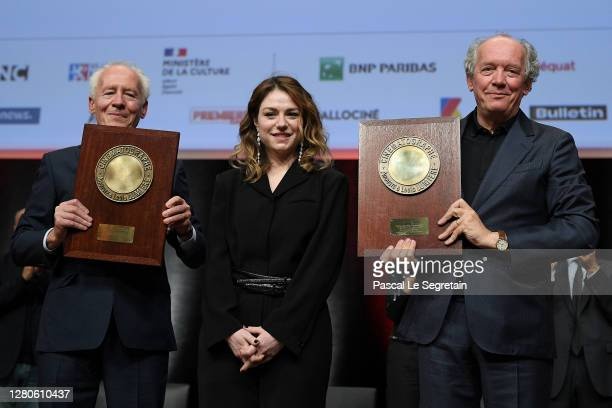 """Luc Dardenne and Jean-Pierre Dardenne pose for a picture with Emilie Dequenne on stage holding their award """"Prix Lumiere"""" during the tribute to the..."""