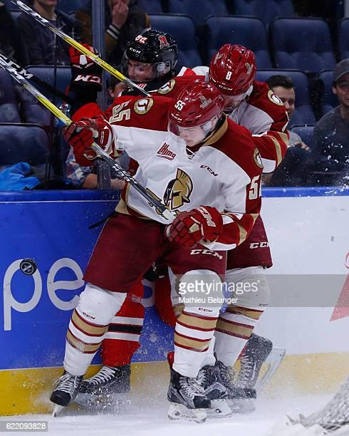 Luc Deschenes and Olivier Desjardins of the Acadie-Bathurst Titan hit Jesse Sutton of the Quebec Remparts during their QMJHL hockey game at the...
