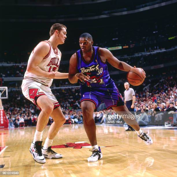 Luc Longley of the Chicago Bulls defends Oliver Miller of the Toronto Raptors on December 22 1995 at the United Center in Chicago Illinois NOTE TO...