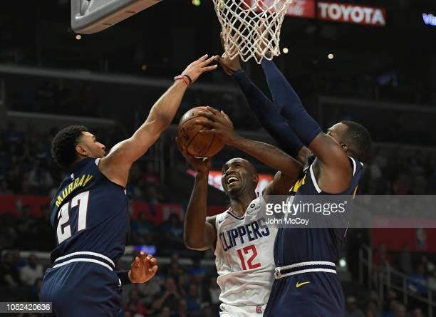 Luc Mbah a Moute of the LA Clippers is guarded by Jamal Murray and Paul Millsap of the Denver Nuggets in the first half during the season opening...