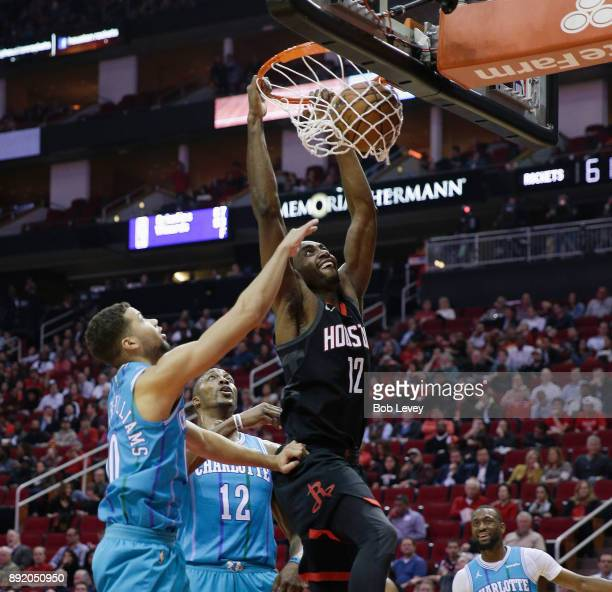 Luc Mbah a Moute of the Houston Rockets dunks as he splits Dwight Howard of the Charlotte Hornets and Michael CarterWilliams at Toyota Center on...