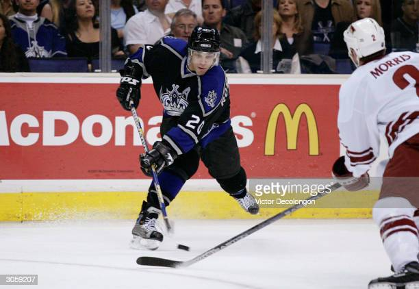 Luc Robitaille of the Los Angeles Kings takes a slap shot on goal as Derek Morris of the Phoenix Coyotes tries for the deflection in the first period...