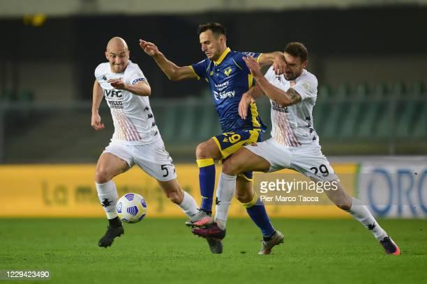 Luca Caldirola of Benevento Calcio and Pasquale Schiattarella of Benevento Calcio compete for the ball with Nikola Kalinic of Hellas Verona FC during...