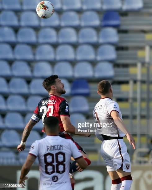 Luca Ceppitelli of Cagliari competes with Andrea Belotti during the Serie A match between Cagliari Calcio and Torino FC at Sardegna Arena on June 27...