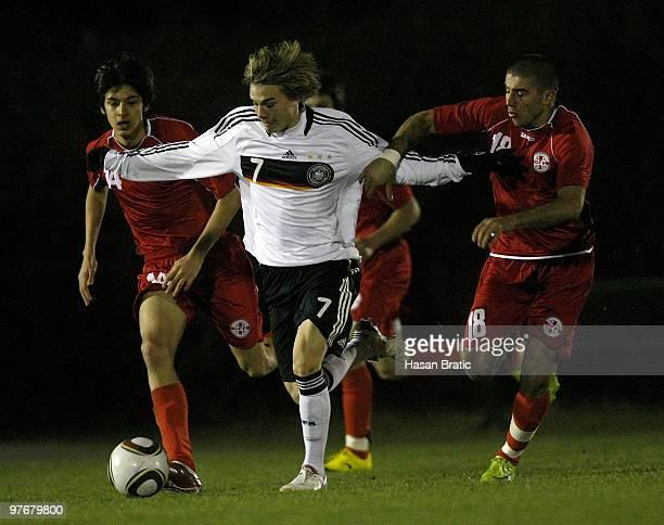 Luca Duerholz of Germany battles for the ball with Lasha Parunashvili and Giorgi Khubua of Georgia during the Internatinal Friendly match between U17...