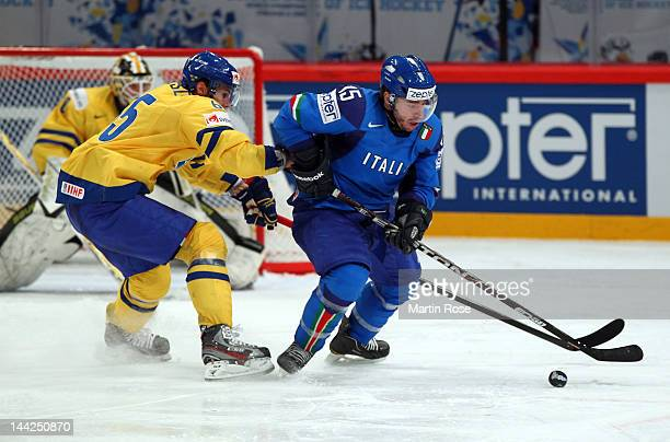 Luca Felicetti of Italy and Erik Karlsson of Sweden battle for the puck during the IIHF World Championship group S match between Italy and Sweden at...