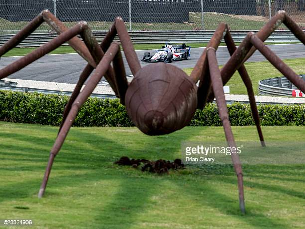 Luca Filippi of Italy drives the Honda IndyCar past a spider sculpture during practice for the Honda Indy Grand Prix of Alabama at Barber Motorsports...