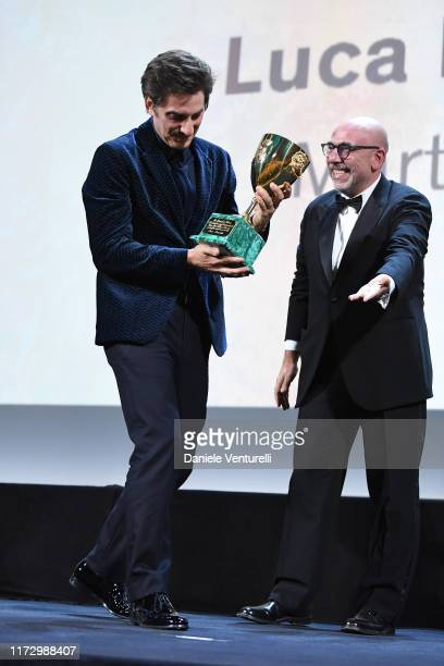 """Luca Marinelli receives the Coppa Volpi for Best Actor Award for """"Martin Eden"""" from Main Competition Jury Member Paolo Virzi during the Award..."""