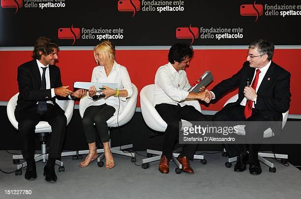 Luca Peyrano and Vic Annels hand the UKItaly Creative Industries Award to producers Tiziana Soudani and Carlo CrestoDina during the 69th Venice Film...