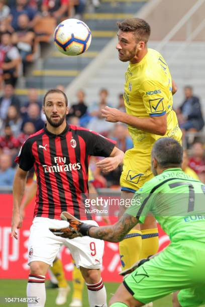 Luca Rossettini of AC Chievo Verona competes for the ball with Gonzalo Higuain of AC Milan during the serie A match between AC Milan and Chievo...