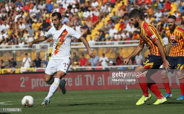 Luca Rossettini of Lecce competes for the ball with Henrick Mkhitaryan of Roma during the Serie A match between US Lecce and AS Roma at Stadio Via...