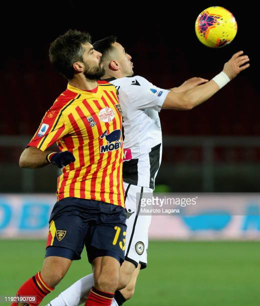 Luca Rossettini of Lecce competes for the ball with Rodrigo De Paul of Udinese during the Serie A match between US Lecce and Udinese Calcio at Stadio...