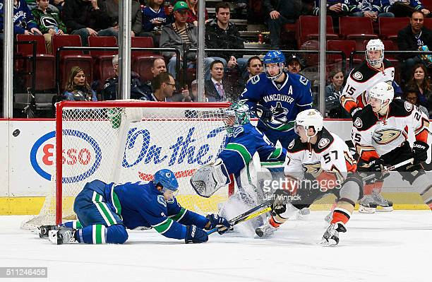 Luca Sbisa and Ryan Miller of the Vancouver Canucks watch the deflection by David Perron of the Anaheim Ducks miss the net during their NHL game at...