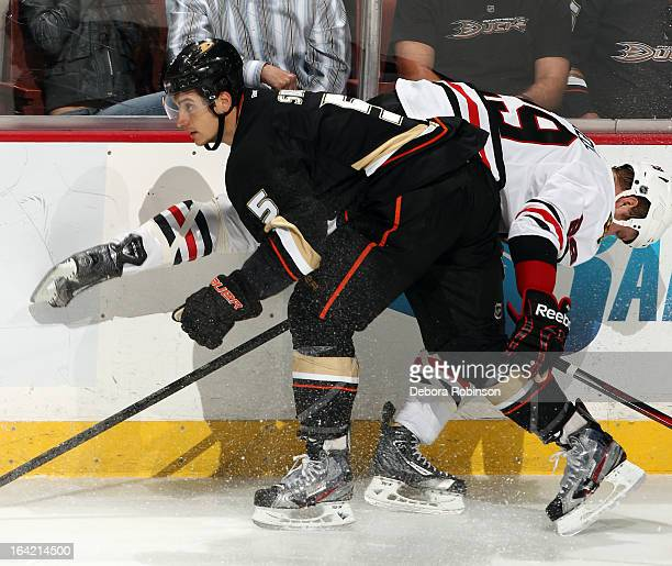 Luca Sbisa of the Anaheim Ducks checks Bryan Bickell of the Chicago Blackhawks into the boards during the game on March 20 2013 at Honda Center in...