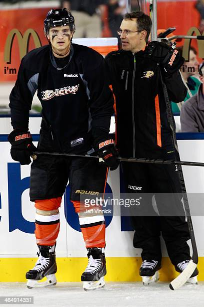 Luca Sbisa of the Anaheim Ducks talks to assistant coach Scott Niedermayer during team practice for the 2014 Coors Light NHL Stadium Series against...