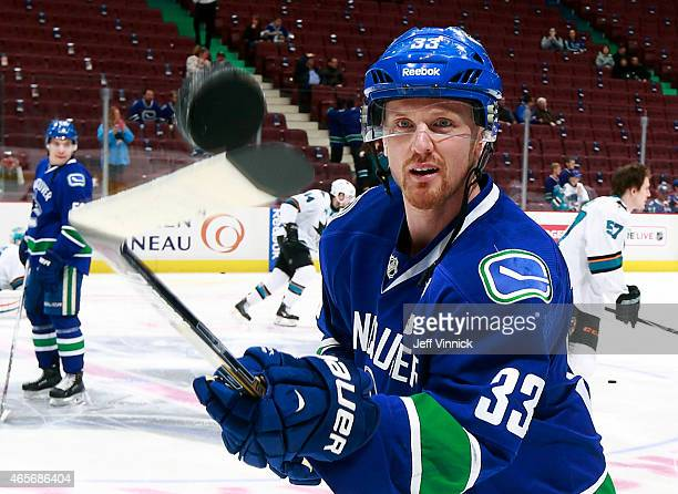 Luca Sbisa of the Vancouver Canucks and Joe Pavelski of the San Jose Sharks watch a loose puck during their NHL game at Rogers Arena March 3 2015 in...