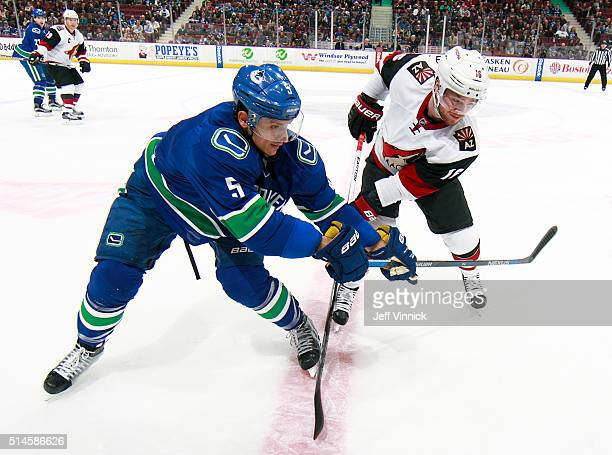 Luca Sbisa of the Vancouver Canucks checks Max Domi of the Arizona Coyotes during their NHL game at Rogers Arena March 9 2016 in Vancouver British...