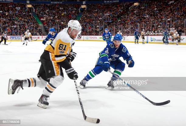 Luca Sbisa of the Vancouver Canucks looks on as Phil Kessel of the Pittsburgh Penguins skates up ice with the puck during their NHL game at Rogers...