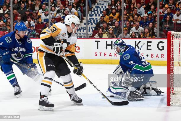 Luca Sbisa of the Vancouver Canucks looks on as teammate Ryan Miller blocks a shot from Conor Sheary of the Pittsburgh Penguins during their NHL game...