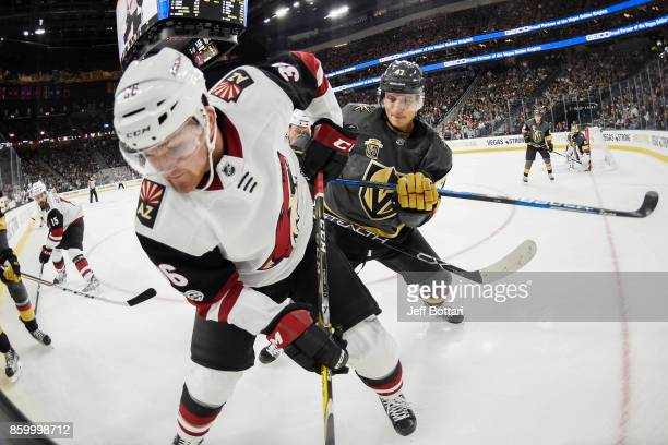 Luca Sbisa of the Vegas Golden Knights defends Christian Fischer of the Arizona Coyotes along the boards during the Golden Knights' inaugural...