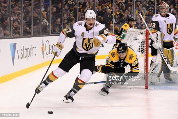 Luca Sbisa of the Vegas Golden Knights skates with the puck against David Pastrnak of the Boston Bruins at the TD Garden on November 2 2017 in Boston...