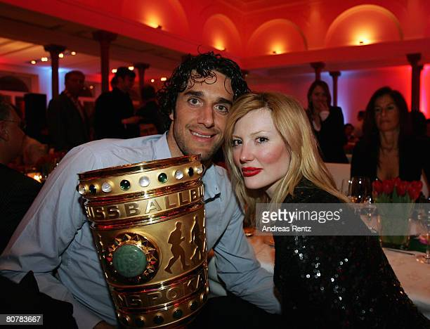 Luca Toni and girlfriend Marta Cecchetto hold the trophy at the the Bayern Munich champions party after the DFB Cup Final match between Borussia...
