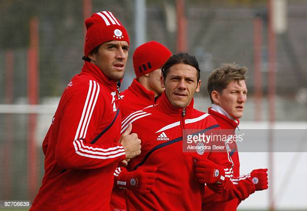Luca Toni Martin Demichelis and Bastian Schweinsteiger of Bayern Muenchen warm up during a training session on November 4 2009 in Munich Germany...