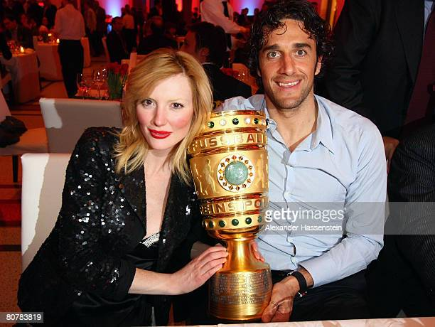 Luca Toni of Bayern Munic poses with his girlfriend Marta Cecchetto and the DFBTrophy during the Bayern Munich champions party after the DFB Cup...