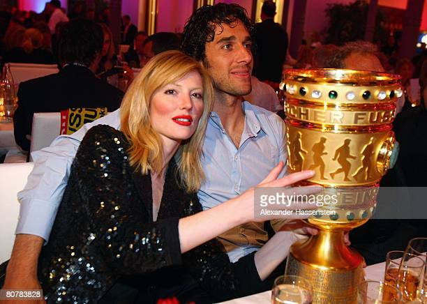 Luca Toni of Bayern Munich poses with his girlfriend Marta Cecchetto and the DFBTrophy during the Bayern Munich champions party after the DFB Cup...