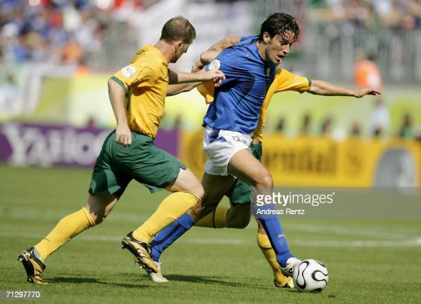 Luca Toni of Italy is challenged by Scott Chipperfield of Australia during the FIFA World Cup Germany 2006 Round of 16 match between Italy and...